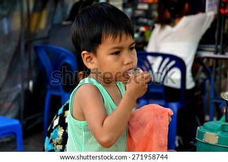 Bangkok, Thailand - December 21, 2009:  Little boy sucks on an ice cube to keep cool at on outdoor restaurant on Thanon Chakrabongse