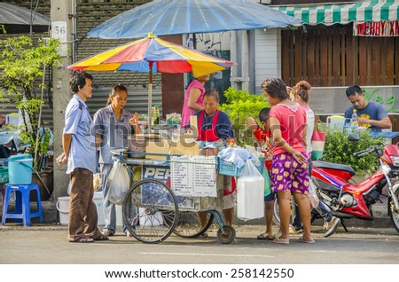 BANGKOK, THAILAND, DECEMBER 26, 2012: Local people buy food and drinks from street seller - stock photo