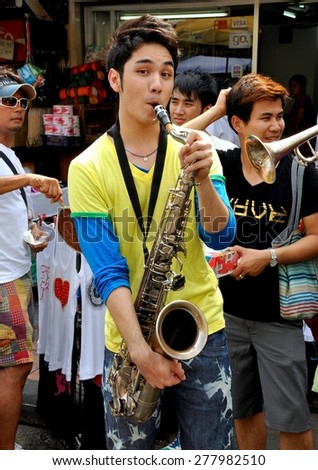 Bangkok, Thailand - December 15, 2010:  Musician playing his saxophone performs with a group at an impromptu concert on Khao San Road - stock photo