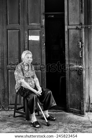 BANGKOK, THAILAND - DECEMBER 25, 2014: Street Photography of old woman with a cane in her hands sitting on a chair near the door of her house - stock photo