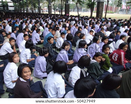 BANGKOK, THAILAND - DECEMBER 20 : Students sit outside for morning assembly at Seekan school December 20, 2005 in Bangkok. - stock photo