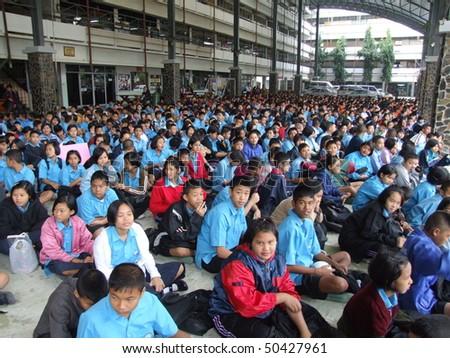 BANGKOK, THAILAND - DECEMBER 21 : Students sit outside for morning assembly at Seekan school December 21, 2005 in Bangkok. - stock photo