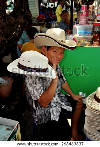 Bangkok, Thailand - December 30, 2010:  Thai vendor selling cowboy hats at the Tha Chang Pier outdoor market
