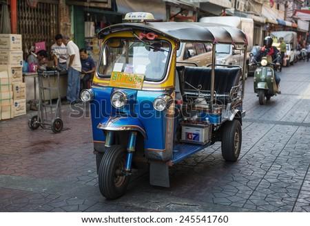 "BANGKOK, THAILAND - DECEMBER 25, 2014:Traditional street taxi ""tuk-tuk"" awaits passengers on a street in Chinatown in Bangkok. In Bangkok, there are more than 100,000 ""tuk-tuk."" - stock photo"