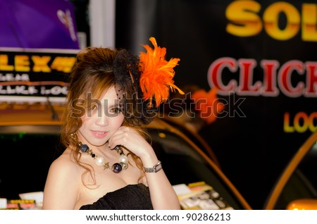 BANGKOK, THAILAND - DECEMBER 6: Unidentified female presenter at Solax booth in THE 28th THAILAND INTERNATIONAL MOTOR EXPO 2011 on December 6, 2011 in Bangkok, Thailand. - stock photo