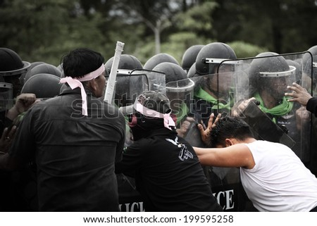 BANGKOK THAILAND-DECEMBER 10 :  Unidentified  protester push the Police in Riot Gear during a violent anti-government on dec 10, 2013 in Bangkok, Thailand. - stock photo