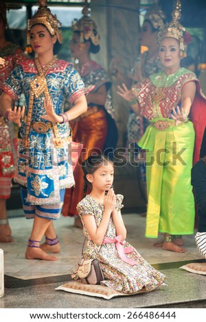 BANGKOK,THAILAND - DEM 21 : Unidentified girl make a votive offering the Brahma by present Thai style musical and Thai dancing at Ratchaprasong intersection on December 21, 2014 in Bangkok, Thailand. - stock photo