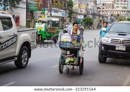 BANGKOK, THAILAND - FEB 20, 2015: Fruit vendor in the streets of the city trades with trolleys. Small business is booming in the Thai capital - stock photo