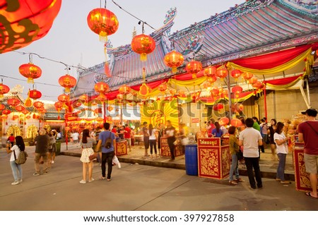 BANGKOK, THAILAND - FEB 14: Red lanterns over people in courtyard of Chinese style Buddhist temple on February 14, 2015. Population of Bangkok is over 8 million, most populous city of Thailand - stock photo
