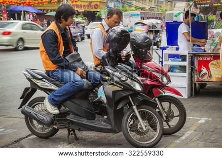 BANGKOK, THAILAND - FEB 20, 2015: Taxi drivers on scooters waiting for customers in Bangkok. Motorbike taxis are a popular choice for the Thai  heavily congested roads - stock photo