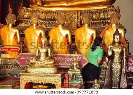 BANGKOK, THAILAND - FEB 14: Woman wears a cloth on the statue of the Golden Buddha of historical monastery Wat Pho on February 14, 2015. Wat Pho is a Buddhist temple complex founded in 16th century