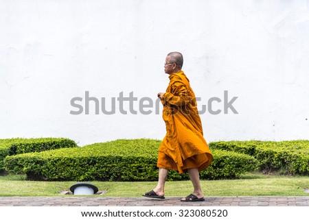 BANGKOK, THAILAND - FEBRUARY 22: A Buddhist monk walks towards the temple gate at Wat Pho on February 22, 2015 in Bangkok, Thailand. - stock photo