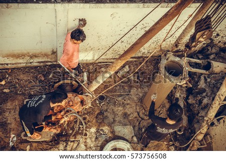 Bangkok, Thailand - February 07, 2017 : Asian construction workers installing wet-process bored pile for house construction. vintage photo and old film style.