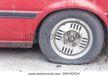 Bangkok, THAILAND - February 6 : flat tire on car wheel in Bangkok, Thailand on February 6, 2012.The old red car flat tire on the road