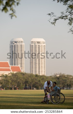 Bangkok, Thailand - February 7, 2015 : Husband older being help wives also fitness walking. He did it as a routine. The place is Sanamluang and background is two skyscraper. - stock photo