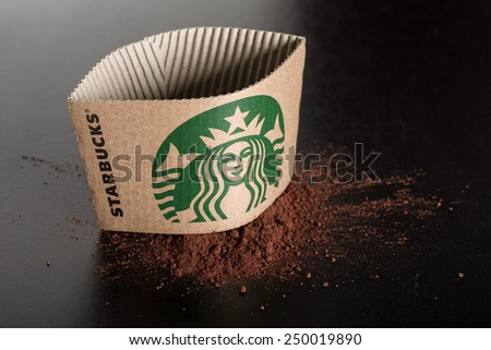 BANGKOK, THAILAND - FEBRUARY 04, 2015: Starbucks coffee cup sleeve and cocoa powder on black board. Starbucks is the world's largest coffee house with over 20,000 stores in 61 countries. - stock photo