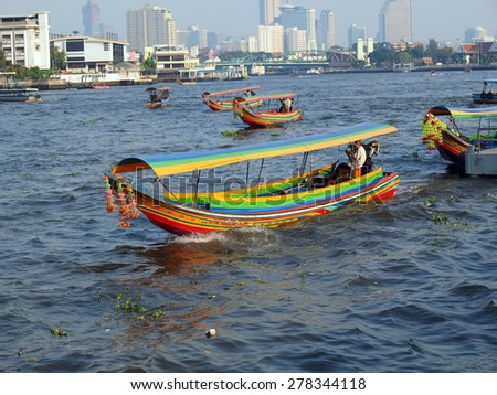 BANGKOK, THAILAND - FEBRUARY 10 : typical long tail boat on Chao Praya river in Bangkok on 10 February 2015. The river is a transportation artery for a  network of water buses and taxis                - stock photo