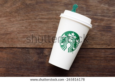 BANGKOK, THAILAND - FEBRUARY 26, 2015: White paper cup with Starbucks logo. Starbucks is the world's largest coffee house with over 20,000 stores in 61 countries. - stock photo