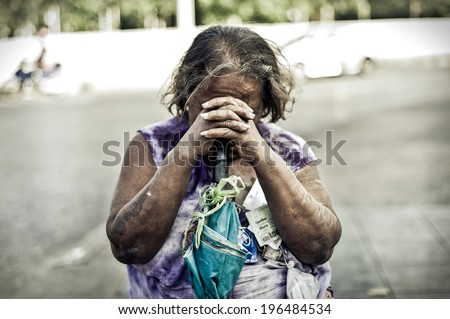 BANGKOK, THAILAND - JAN 24: A homeless woman sits beside the road to rest after begging to the people passing by on JANUARY 24, 2010: in Pak Klong Talad Flower Market - stock photo