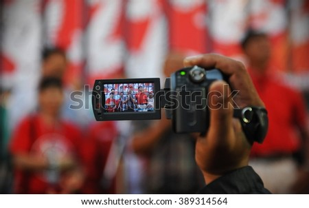 BANGKOK, THAILAND - JAN 29, 2013: An unidentified protester uses a camcorder to video a large city centre Red Shirt rally. The protesters gathered to call for freedom of speech laws. - stock photo