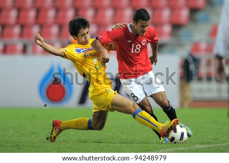 BANGKOK THAILAND-JAN18: Harmeet Singh of  Norway  (red) in action during the 41st King's cup  between Thailand and Norway at Rajamangala stadium on Jan 18, 2012 in Bangkok,Thailand. - stock photo