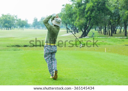 Bangkok,Thailand-Jan 20,Man golf player with driver teeing-off from tee-box to shoot , view from behind on Jan 20,2016. - stock photo