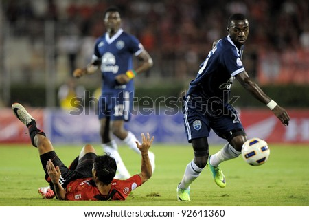 BANGKOK, THAILAND - JAN 11:  Obama Joseph Florent of the Buriram PEA (R) in action during the Thaicom FA Cup Final match  between MuangThong United at National Stadium on Jan11,2012 in Bangkok Thailand. - stock photo