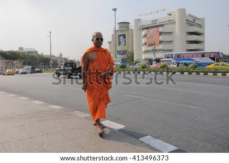 Bangkok, Thailand - January 25, 2011: A Buddhist monk walks along a city centre street. Thailand has about 300,000 ordained monks, with Theravada Buddhism being practised by 95% of the population.