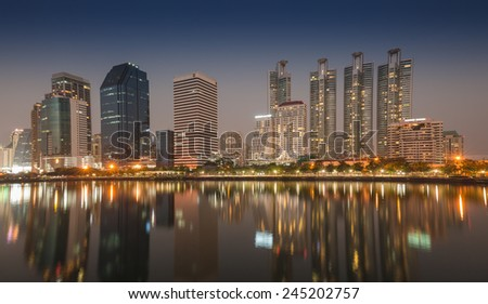 BANGKOK, THAILAND-JANUARY 18 : Business skyscraper skyline is in Bangkok city downtown at night time with reflection on wide lake in Bangkok, Thailand Jan 18, 2015
