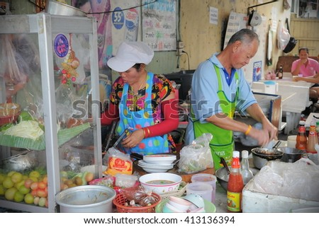 Bangkok, Thailand - January 20, 2011: Cooks prepare food at a city centre street-side restaurant. Government statistics indicate there are over 16,000 registered street vendors in the Thai capital. - stock photo