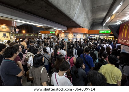 Bangkok, Thailand - January 18, 2016 : Crowd of people walking out from the BTS Mo Chit station to the road in the rush hour at night with the ticket machine in the center. - stock photo
