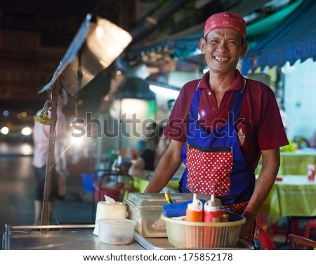 BANGKOK, THAILAND - JANUARY 9, 2012: Local man stands behind his street food stall and smiles to the camera. Everyday thousands of tourists and locals buys food on these stalls. - stock photo