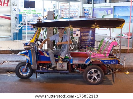 BANGKOK, THAILAND - JANUARY 9, 2012: Local tuk-tuk driver waits for customers. Tuk-tuks have become one of Bangkok's most recognisable transportation features, and are still popular among tourists. - stock photo