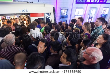 BANGKOK, THAILAND - JANUARY 10, 2012: People at crowded BTS Skytrain station entering the train. 600,000 passengers ride the Skytrain daily. - stock photo