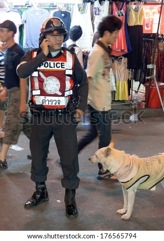 BANGKOK, THAILAND - JANUARY 9, 2012: Policeman on Khao San Road talks on the phone. Royal Thai Police counts about 230,000 officers.