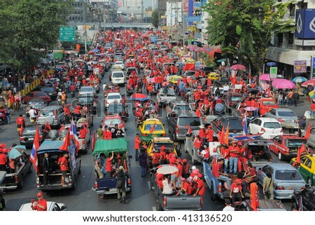 Bangkok, Thailand - January 23, 2011: Protesters in a convoy drive through the city centre Ratchaprasong junction during a large anti government Red Shirt rally.  - stock photo