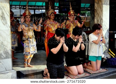 Bangkok, Thailand - January 13, 2013:  Thai Buddhists kneeling with clasped hands pray in front of a group of Khong dancers at the sacred Erawan Shrine - stock photo