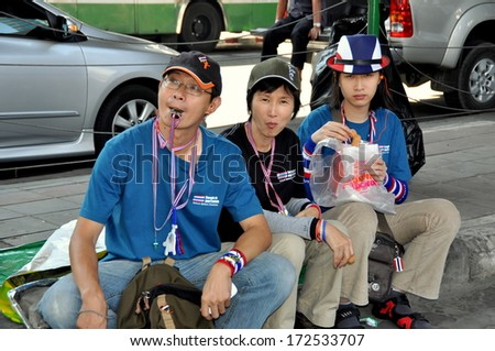 Bangkok, Thailand January 15, 2014:  Thai family sitting on Sukhamvit Road at Asok wearing whistle necklaces during a Shut Down Bangkok rally