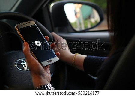 BANGKOK, THAILAND -JANUARY 1 2017. Uber application display on mobile screen in female hands while she want to call or find some Uber (focus on mobile app)
