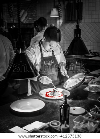 BANGKOK, THAILAND - January 16, 2016: Young chef prepares entree for the client in a busy Italian Tuscan kitchen - stock photo