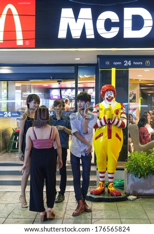 BANGKOK, THAILAND - JANUARY 9, 2012: Young local people stand in front of the McDonald's Restaurant at night. There are over 160 McDonald's restaurants in Thailand. - stock photo