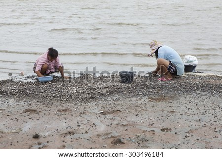 Bangkok, Thailand - Jul 17, 2015: Poor Thai fishers earn their living by collecting clam on the bank of a lake in the summer sunlight.