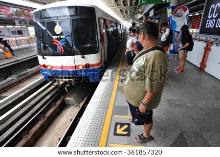 BANGKOK, THAILAND - JUL 17, 2013: Rail travelers wait for a train on a city centre train station platform. Launched in 1999, the BTS currently has a daily ridership of around 600,000 passengers. - stock photo