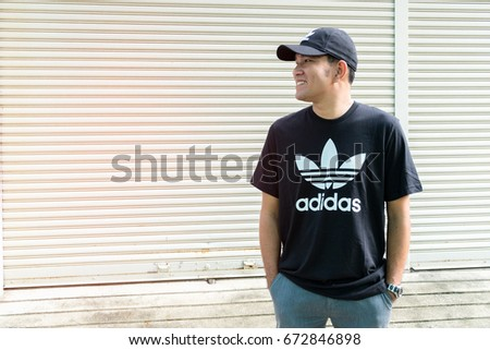 BANGKOK, THAILAND - JULY 2, 2017: Adidas logo on man T-shirt and cap. Adidas is German designer and manufacturer of sports clothing and accessories; largest in Europe and 2nd biggest in the world.