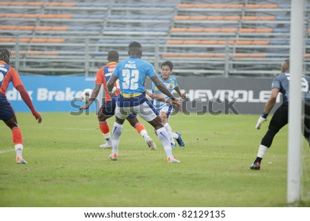 BANGKOK THAILAND- JULY 30 :L.Takam (c) in action during Thai Premier League (TPL) between thai port fc (Orange) vs Pattaya Utd. (Blue) on July 30, 2011 at PAT Stadium in Bangkok Thailand