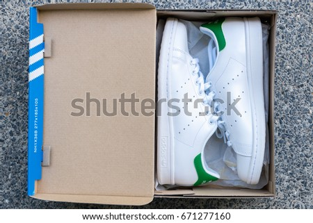 BANGKOK, THAILAND - JULY 2, 2017: Open box adidas stan smith classic shoes on ground stone outdoor popular fashion thailand.