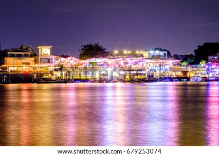 Bangkok, Thailand - JULY 17, 2017: Tha maharaj shopping mall and restaurant at night nearby the Grand Palace on the Chao Phraya River. Local boat at the pier, Bangkok, Thailand.
