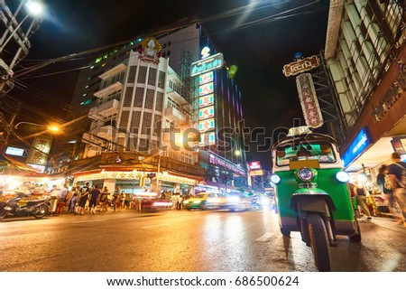Bangkok, Thailand - 21 July, 2017: Tourist People in night life and Tuk-Tuk (Thai taxi) on the Yarowat Road with transport movement in urban and building of Chinatown at night ,Bangkok, Thailand.
