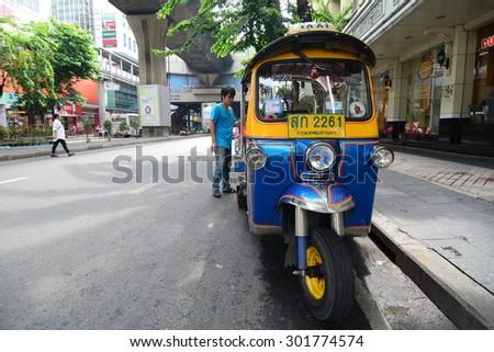 """BANGKOK, THAILAND - JULY 29, 2015: Traditional street taxi """"tuk-tuk"""" awaits passengers on a street in Chinatown in Bangkok. In Bangkok, there are more than 100,000 """"tuk-tuk."""" - stock photo"""