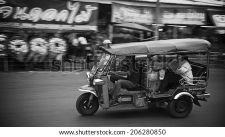 BANGKOK, THAILAND - JULY 18, 2014: Unidentified driver and passenger in tricycle called tuk tuk along street near fresh flower market. Tuk tuk is very good transmission for traffic jam in the city. - stock photo